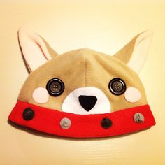 A brown dog beanie/plushy hat! It's made out of soft, kind of stretchy polar fleece! The blush marks, muzzle, nose and studs on its collar are made out of felt, and is securely hot glued on. The eyes are black buttons, and are also securely affixed with hot glue.    The hat would fit on a head wi...