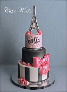 Fondant with gum paste bow and ribbon roses.  Eiffel tower is royal icing piped on gum paste.  Faux bling was used on the base of the top and bottom tier.