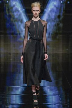 Surprising pop of sheer under a firmly grounded grey wool circle skirt dress. Black belt adds a hint of interest to the waist. Only the confident need apply.