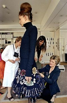 A seamstress overseeing the fitting a dress from Chanel Fall/Winter 2002 Haute Couture