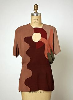 """Evening ensemble, silk. Gilbert Adrian. 1945. In February 1945 Adrian was awarded the third annual American Fashion Critics Award. Thirty-two of the designer's garments were displayed at the award ceremony, including this ensemble which was part of his """"Modern Museum"""" collection. With a palette inspired by Cubism, Adrian extended the abstractions of his earlier designs of the 1940s."""