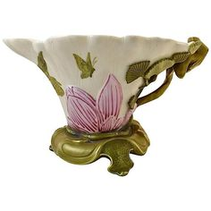 An ivory porcelain decorative bowl, or sauce boat, from Royal Worcester of England, hand-painted with Japanese-style motifs from the natural world including a crane, dragonfly, butterflies, flowers, and foliage; ornament popular during the Aesthetic Movement, Victorian era, and Art Nouveau periods. Circa 1880.