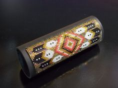 "Native American Beaded Leather Hair Wrap With In A Golden Feather And Flame Pattern Is Made With The Blends Of Shimmering Golds And Fire. This finely detailed American Indian beaded Hair Wrap is the perfect gift for anyone who rides a motorcycle, horseback rides, or just wears there hair in a pony tail! This American Indian beaded hair wrap with a golden feather and flame pattern is made with the blends of shimmering golds with a splash of fire colors of the Southwest. The hair wrap is made of soft oil tanned black leather (approximately 2 mm thick) with 4 heavy duty snaps. Inside the hair wrap is a metal hook riveted to the leather. Glass Delica 15/0 seed beads (1 mm each) are then woven with patience and care and carefully sewn onto the leather hair wrap in this classic pattern. Each end of the beaded pattern is ""triple stitched and the end strings are then bonded together. This is done to ensure that the beads do not come apart during the years of wearing it. The bead work measures Approximately 1 1/4"" wide and is Approximately 3 3/4"" long for a total of 1,725 beads! This hair wrap measures 4 inches long and custom orders for longer hair wraps are available. How to wear your hair wrap: Simply put your hair up in a regular elastic pony tail holder. Hook your new hair wrap onto the elastic pony tail holder with the hook located inside the hair wrap, then wrap the leather hair wrap around your pony tail and snap, and wait for the complements on your beautiful beaded hair wrap! I enjoyed creating the bead work on this piece of finely detailed Native American jewelry. This hair wrap is signed and comes with a certificate of Authenticity. Thank you for looking at my beaded jewelry."