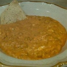 This simple cheese and chili dip is great with tortilla chips or French bread. It may be prepared and served in a slow cooker, if desired. A fondue pot also works well for keeping the finished dip warm.