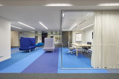 Brightly patterned carpeting and flooring with booth-like couches at Astrazeneca Offices, Barcelona