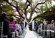 Woodland wedding ceremony backdrop: Fabric Draped Tree With Hanging Flower Baskets