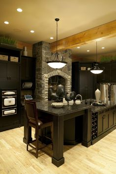 Luxury black kitchen with 2-tier island and light wood ceiling beams.