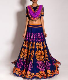A stunning midnight blue lehenga embellished with orange and purple kanjivaram appliqué work. The lehenga is accompanied with a matching blouse and an orchid dupatta with orange kanjivaram appliqué and an embroidered border in dull gold.