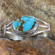 This beautiful Sterling Silver Bracelet features Number 8 Turquoise from Eureka County north of Carlin Nevada. This artistic piece of jewelry is handcrafted by Navajo jewelers and silversmiths. Colors