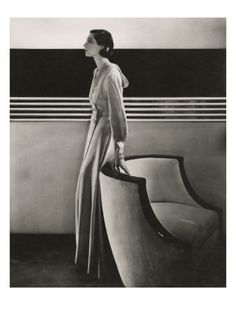 Model Ilka Chase stands in a well-appointed formal room, resting her hand on a chair. She wears a long moiré housecoat, paired with jewels from Black Starr and Frost-Gorham and a hairstyle created by Laurent. Her draped ensemble contrasts nicely with the clean lines of the back wall. Edward Steichen's black and white fashion photograph appeared in the November 15, 1933, Vogue.