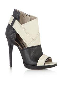 Deze sandaal Lara van McQ Alexander McQueen is uitgewerkt met een contrast. Dit model met hoge stiletto sluit met een rits, en heeft vlakken in generfd leer en nubuck. De stikselversieringen maken de schoen helemaal af.