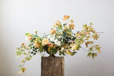 The altar will be flanked by gold compotes with tall, overflowing arrangements of red zinnias, orange waxflowers, cherry brandy roses, peach ranunculus, orange rosehips, yellow solidago, scabiosa pods, blue gray succulents, and orange clovers.