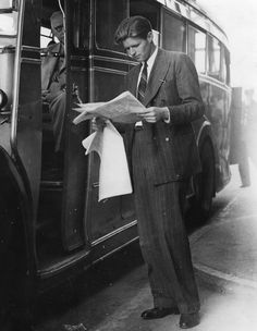 Joseph P Kennedy Jr., son of the American ambassador and brother of John F Kennedy, stands by a coach, reading a newspaper, at Croydon bus garage, where he has arrived from Hamburg. (Photo by Keystone/Getty Images)