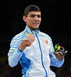 Uzbekistan's Murodjon Akhmadaliev poses on the podium with a bronze medal during the Rio 2016 Olympic Games at the Riocentro - Pavilion 6 in Rio de Janeiro on August 20, 2016.   / AFP / Yuri CORTEZ