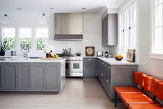 "A 1960s-era flame-colored bench stands out in the serene gray kitchen. ""It makes it that much more interesting and feels clean yet retro,"" says Perera."
