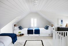 Perfect for sleepovers, this shiplap attic kids' room is furnished with end to end white built in storage beds accented with black leather pulls and white bedding finished with a blue throw blanket and blue pillows.