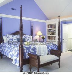 BEDROOM -vaulted ceiling, periwinkle blue walls with quilt spread to match, dark wood  four poster bed, plantation style, bench bookshelves.  View Large Photo Image