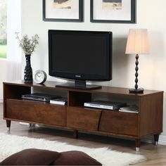 This beautiful Venus 70-inch entertainment center will bring stylish function to your living room or den. With a low-profile design and rich autumn oak finish, this versatile cabinet features two large storage drawers for organizing media accessories.