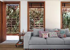 Para a sala parecer maior: as esquadrias de freijó com batentes de cumaru (SD Marcenaria) ligam o ambiente com o jardim vertical. O peitoril de 60 cm (mais baixo que o usual) propicia ampla integração