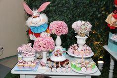 Mesa de doces com enfeite da festa Alice no País das Maravilhas