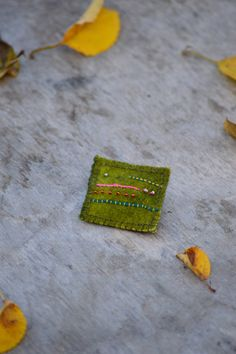Handmade woolen brooch with handmade embroidery and glass