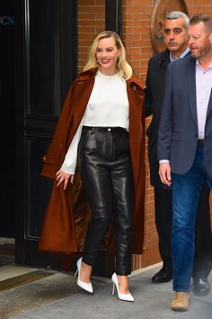 Ever one to pull off a polished look, Margot Robbie updated a classic black-and-white palette  with a rust Acne trench coat (Sarah Flint's powdery, white pumps, Magda Burtrym's high-rise pants (now on sale), and a white long-sleeve top. Acne Studios' trench coat.) #streetstyle #newyorkstyle2020 #falltrends Patent Leather Leggings, Leather Blazer, Margot Robbie Style, Skin Tight Leggings, High Rise Pants, White Pumps, Polished Look, Coat Dress, Alter