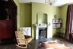 The living room features an unexpected mix of pea green and deep purple.