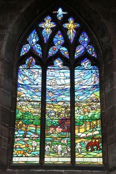 Nantwich/Cheshire/Engeland - St. Mary's Church. Het nieuwste glas heeft de totale schepping als thema. Dieren, landschappen, het uitspansel - en de mens, als Adam en Eva in het paradijs, in de personen van de overleden (lokale landbouwer) Albert Stanley Bourne (1981) en zijn vrouw Betty, die dit glas in 1985 opdroeg aan de kerk als nagedachtenis aan haar man, en 'To the glory of God' (de hand van god is zichtbaar bovenin). Michael Farrar-Bell maakte het. Foto: G.J. Koppenaal - 15/6/2015.