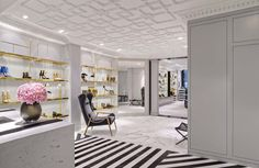 Aquazzura store in London Mayfair with interior design and architecture of Casa do Passadiço. Black and white. Golden shelves. Straight lines. Shoe store. Marble.