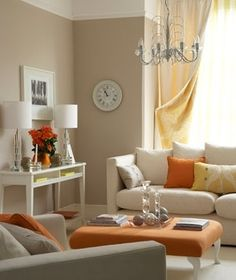 The application of orange and cool grey in this living room set ...