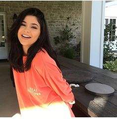 Wheretoget - Kylie Jenner wearing a large coral pink tee-shirt with printed words