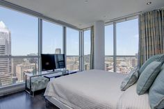 This contemporary bedroom design offers elegance and stunning panoramic views of the city.