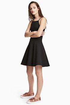 Krátke šaty zo štruktúrovaného džerseja stenkými ramienkami, švom vpáse azvonovou sukňou. Hlboký výstrih na chrbte shorizontálnym prúžkom látky cez šiju