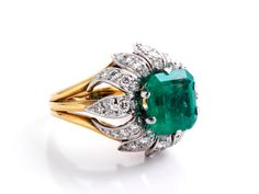 Emerald ring with diamonds Ring size: 55. Weight: ca. 13.1 g. 18 ct yellow gold. Blossom ring with Colombian square emerald-cut emerald, ca. 3.7 ct, and small brilliant-cut diamonds, altogether ca. 1 ct. emerald with minor nicks along the edge.