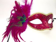 Petite hot pink and gold Mardi Gras mask with peacock feathers and black ribbon ties.