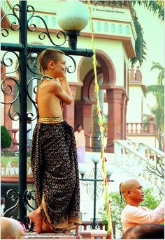 | little monk | This foreigner little monk climbed on the Light Post to view the joyful Rath Yatra and the dance of monk & nun on the eve of Happy Holi or DOL YATRA at ISKCON Temple Mayapur , West ,Bengal , India on the day before Holi , the celebration of Colours .