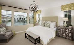 A downstairs master suite with a spacious walk-in closet and spa-like bath - Plan 1104 at Villas at Villa del Lago in Chandler, AZ