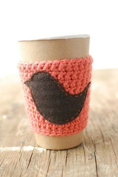 Cup cozy Orange with a bird on it by The Cozy Project.