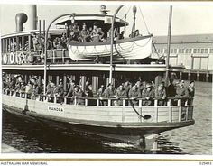 "SYDNEY, AUSTRALIA. 1943-02-27. QUEENSLAND MEMBERS OF THE 9TH AUSTRALIAN DIVISION RETURNING FROM THE MIDDLE EAST BEING FERRIED FROM WOOLLOOMOOLOO, WHERE THEY HAD DISEMBARKED FROM THE TROOPSHIPS ""AQUITANIA"" AND ""ILE DE FRANCE"", TO PYRMONT WHERE THEY WILL ENTRAIN FOR THEIR HOME STATE Source Aust War Memorial"