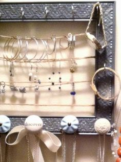 Clever jewelry storage created from a frame, cup hooks and twine.