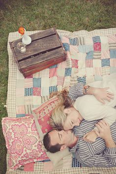 couple cuddling on a pastel color block quilt