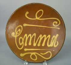 """Pook & Pook.  April 18th 2008. Lot 252.  Estimated: $500 - $1000. Realized Price: $819. Redware charger, 19th c., signed in slip """"Emma"""", 13 1/4"""" dia."""