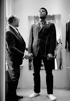 Muhammad Ali is measured for a bespoke suit by a tailor in London's Seville Row, 1966 © Muhammad Ali, photographed by Thomas Hoepker, 1966