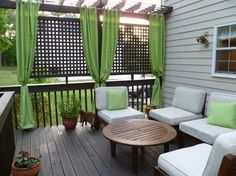 Trellis at the end of our deck with plants growing up it, panel curtains along other side