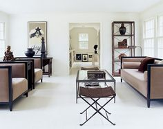 The former sunroom of Joseph Montebello and Ron Leal's 1950s Cape Cod is a now a chic parlor connecting the original building to a new master suite (at rear). Against a white backdrop, every object gets a chance to shine. The owners chose upholstered pieces, from Up Country in Vancouver, with lines as pronounced as those of their neoclassical antiques, a Restoration Hardware coffee table and a pair of X-legged stools from Mexico. The painting is by Ramón Santiago. - ELLEDecor.com