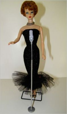 This looks just like my first Barbie.  Mine was blonde but she had the same dress.  My little brother bit off one of her fingers.  She's tucked away in my closet now.
