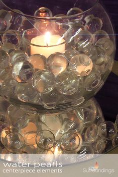 If you want a classic, elegant look to your candle centerpieces, adding pearls is one way to achieve this. Fish Bowl Centerpiece Wedding, Water Pearls Centerpiece, Fishbowl Centerpiece, Candle Centerpieces, Wedding Centerpieces, Fish Bowl Vases, Bead Bowl, Water Gems, Jewelry Center