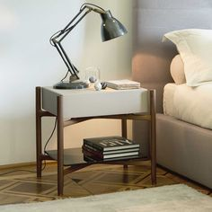An elegant nightstand/end table with the frame in solid walnut. The drawer is either veneered to match the frame or covered in leather (various colors available). A matching set of drawers is also available