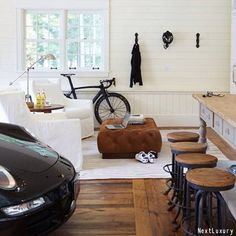 Not every man cave has to be huge! Check out this small and simple man cave in the garage. Great wood details with white walls and chairs, plus black accents like that clean Porsche 911.