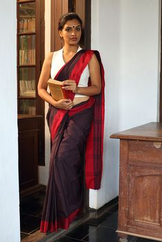 The Kamala Saree - Seamstress This saree is a tribute to the fiery women writers and freedom fighters of Kerala. Strong, bold and classic. This soot black saree has tiny red checks and a red border